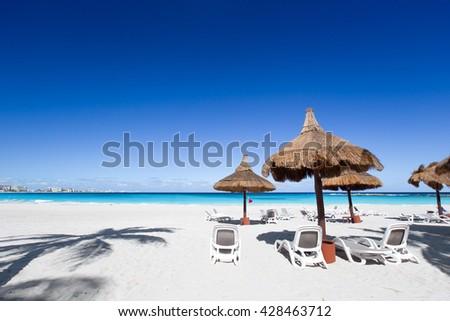 Beach chairs and grass umbrellas on a stunning tourist resort beach - stock photo