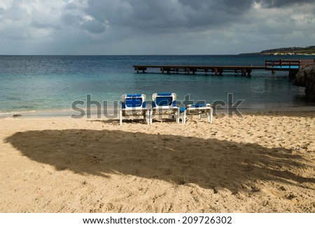 Beach chairs and palapa thatched umbrella overlooking the ocean - stock photo