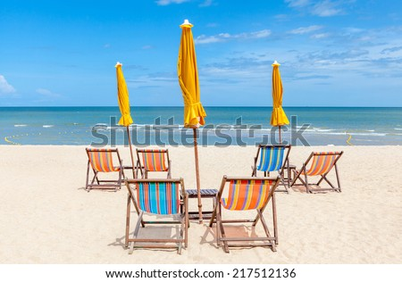 Beach chairs and sun umbrellas on the white sand beach with clear blue sky. Concept for rest, relaxation and holiday. - stock photo