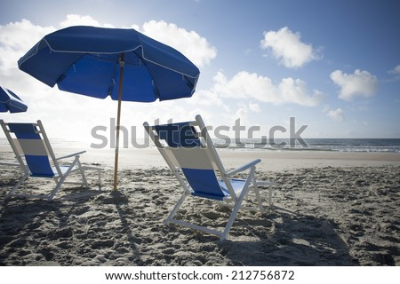 Beach Chairs and Umbrella at the Ocean - stock photo