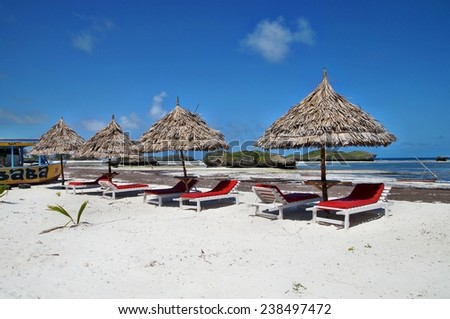 Beach chairs and umbrellas on white sand beach at Watamu near Malindi, Kenya - stock photo