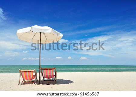 Beach chairs and with umbrella and beautiful beach on a sunny day - stock photo