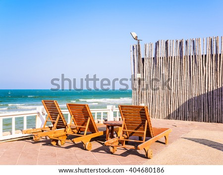 Beach chairs and wood fence on stunning tropical beach