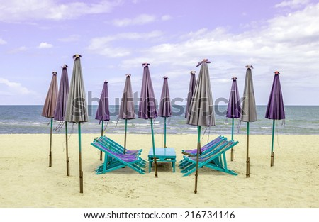 Beach chairs around with closed sun umbrellas on the white sand beach. Concept for rest, relaxation and holiday in Thailand. - stock photo