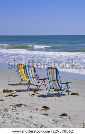 Beach Chairs at the seashore waiting for sunbathers - stock photo
