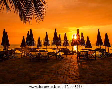 Beach chairs in evening at sunset - stock photo
