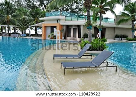 Beach chairs in swimming pool - stock photo