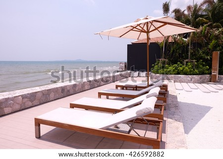 Beach chairs near swimming pool. - stock photo