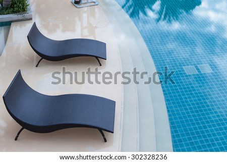 Beach chairs near swimming pool, top view - stock photo