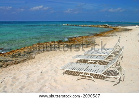 Beach chairs on Seven Miles Beach - stock photo