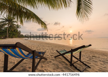 Beach chairs on the sand beach, Beautiful beach and tropical sea at sunset.