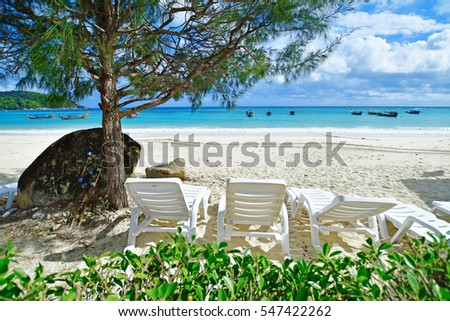 Beach chairs on the white sand beach with cloudy blue sky and sun
