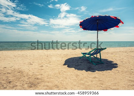 Beach chairs on the white sand under coconut tree beach with cloudy blue sky and sun in vintage style - stock photo