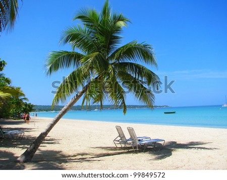 Beach chairs on tropical white sand beach, Negril, Jamaica - stock photo