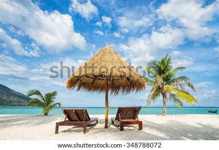 Beach chairs, umbrella and palms on the beach. Thailand. Koh Lipe island. - stock photo