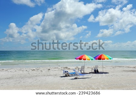 Beach Chairs with Bright Color Umbrellas on the Beach - stock photo