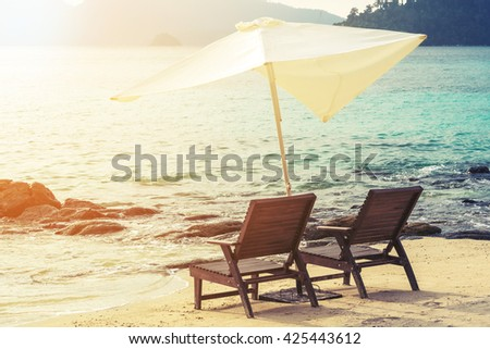 Beach chairs with parasol on the beach, soft focus. vintage tone.holidays vacation - stock photo