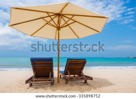 Beach chairs with umbrella and beautiful beach on a sunny day - stock photo
