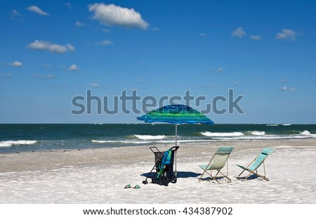 Beach Chairs with Umbrella on a Beautiful Sunny Beach in Florida - stock photo