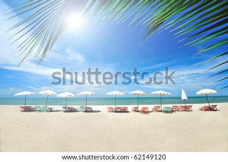 Beach chairs with umbrellas with sunshine - stock photo