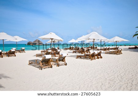 beach chairs with white umbrella at the ocean front