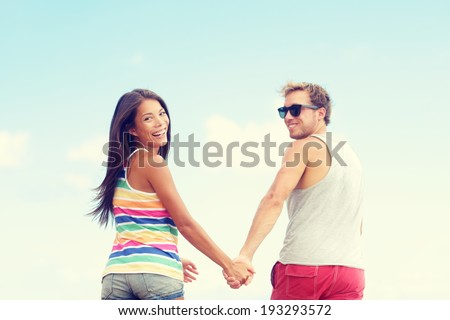 Beach couple enjoying fun romantic vacation holiday. Happy young trendy cool multi-ethnic couple running having fun laughing together smiling happy. mixed race Asian woman, Caucasian man. - stock photo