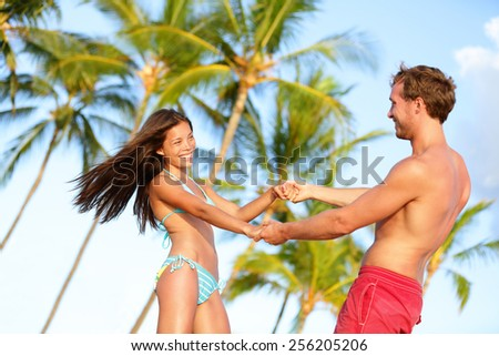 Beach couple fun on vacation dancing playful. Happy young lovers enjoying summer vacation holiday on beach. Beautiful interracial couple in love. Asian woman, Caucasian man on Hawaii. - stock photo