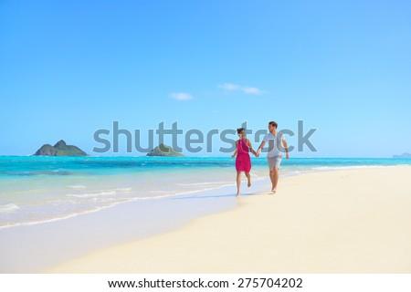 Beach couple happy having fun on Hawaii honeymoon. Romantic couple cheerful and full of happiness on travel vacation, Lanikai beach, Oahu, Hawaii, USA with Mokulua Islands. Asian woman, Caucasian man - stock photo