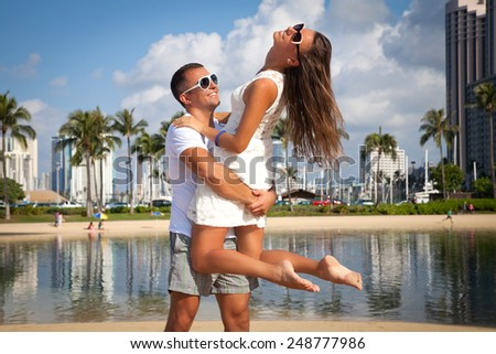 Beach couple in love having vacation summer fun holding each other tightly, smiling happy on tropical beach on Honolulu, Oahu, Hawaii, USA. Romantic young couple at the beach in playful mood.  - stock photo