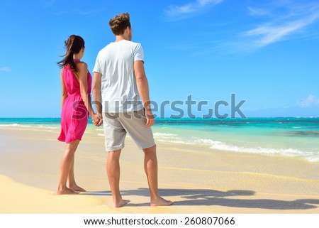 Beach couple looking at ocean view from behind. Unrecognizable couple standing on white sand in pink dress and casual shorts holding hands relaxing on summer travel vacations in tropical destination. - stock photo