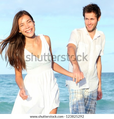 Beach couple walking happy, carefree and joyful on summer vacation. Interracial young couple holding hands. Asian woman, Caucasian man. From Varadero Beach, Cuba. - stock photo