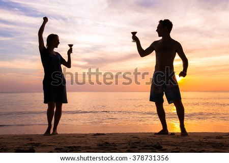 beach festival or party with friends, joyful happy people celebrating life, couple dancing with cocktails - stock photo