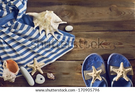 Beach flip flops, striped dress, seashells on a wooden floor. Summer vacations background - stock photo