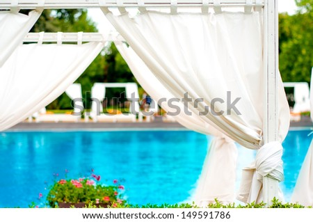 beach front relaxing sunbeds inside tent with fancy pool background - stock photo