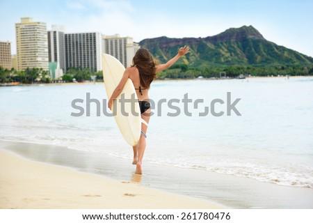 Beach fun - Happy freedom surfer woman going surfing in Waikiki beach, Honolulu city, Oahu, Hawaii, USA. Hawaiian surf girl heading for waves with surfboard living healthy active lifestyle, rear view. - stock photo