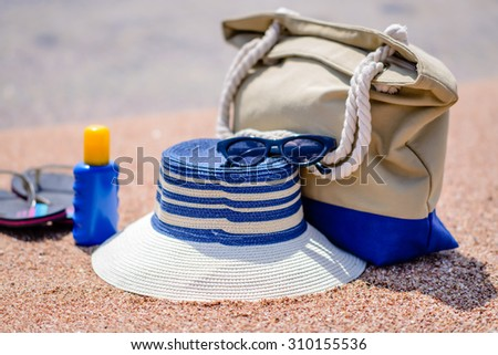 Beach gear on the sand overlooking the sea with a sunhat, sunscreen, slip slops and beach bag conceptual of a summer vacation in the tropics