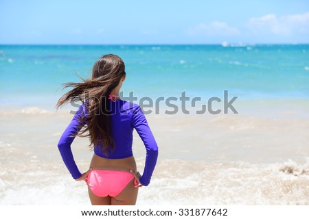 Beach girl going swimming in rashguard swimwear protective clothing. Woman standing in bikini and uv sun protection surf shirt looking at ocean waves. Healthy active lifestyle. - stock photo