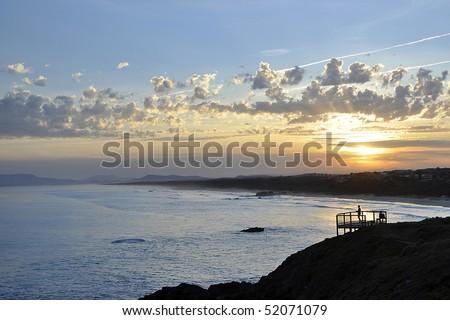 Beach goers watching sunset - stock photo