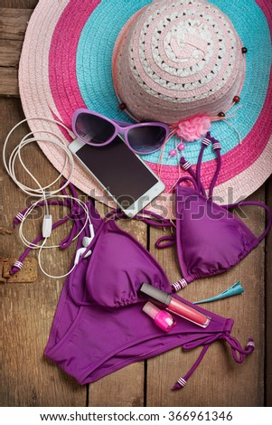 Beach hat and a swimsuit on the old boards - stock photo