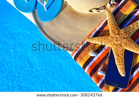 Beach hat, bath towels, cell phone, starfish, thongs near the swimming pool