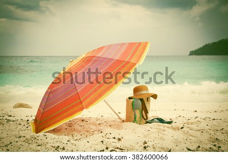 Beach holiday concept. Straw hat and bag on a tropical beach - vintage photo - stock photo