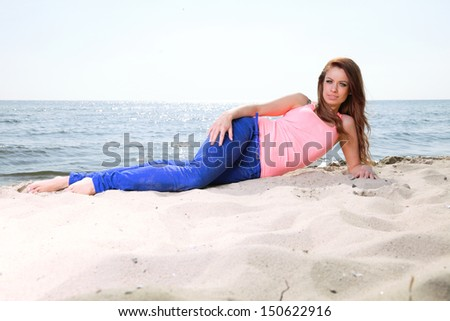 Beach holidays woman enjoying summer sun lie in sand looking happy at copy space. Beautiful young model - stock photo