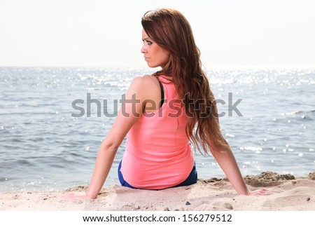 Beach holidays woman enjoying summer sun sitting in sand looking happy at copy space. Beautiful young model - stock photo
