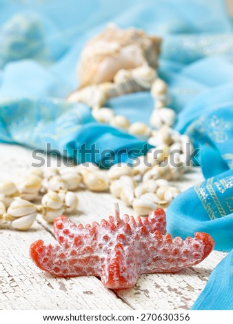 beach house decor, setting summer vacation : Candle in the form of starfish, shells, pareo on the wooden background   - stock photo