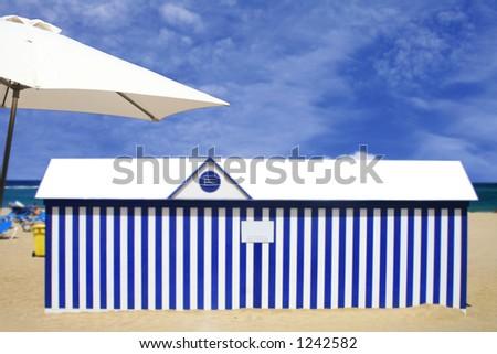 Beach hut with umbrella - stock photo