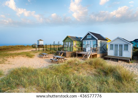 Beach huts in sand dunes on Mudeford Spit near Christchurch on the Dorset coast - stock photo