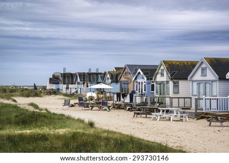 Beach huts on sand dunes and beach landscape  - stock photo
