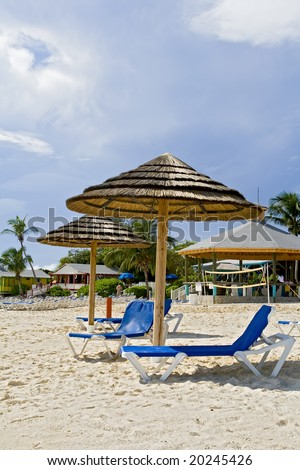 Beach huts on tropical shoreline of a resort. - stock photo