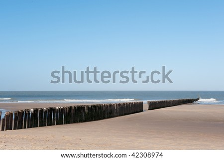 Beach in Holland with wave breaker from wooden poles - stock photo