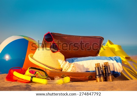 Beach items in vintage suitcase on the sand. Summer vacation concept - stock photo